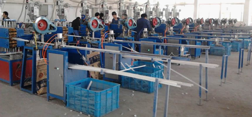 There are many professional workers with blue uniforms manufacturing corner bead.